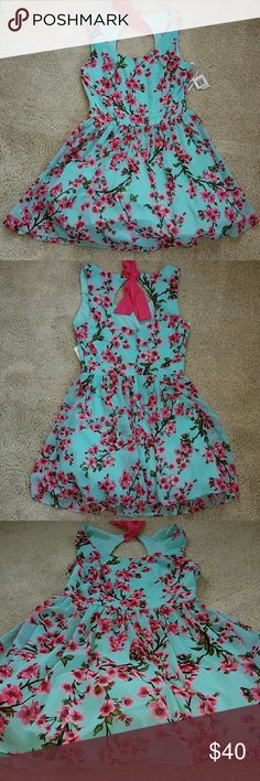 Adorable floral dress Aqua colored sleeveless dress with fushia cherry blossom print. Pink bow that ties at the neck. Skirt has a small tulle layer at the bottom for fullness. New and unworn with tag attached. Fits size 9/10. B Darlin Dresses