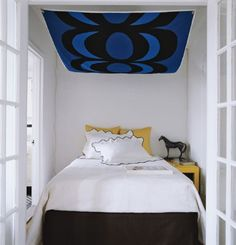 Small bedroom. Large graphic print canopy over bed. Black. Blue. Yellow. White. Horse Sculpture.