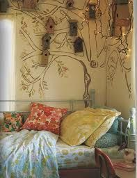Nature inspired bedroom unmatched flower pillow & bed sheets. A wall of bird houses with a painted tree extending branches & leaves. The lights give this bird village a gypsy vibe.