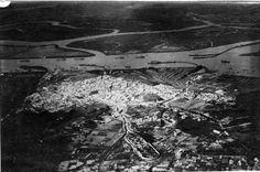 Vista aérea de Huelva capital. En primer plano se puede observar el ya desaparecido Cementerio de San Sebastián. Estaba situado al final de la calle San Sebastián e inicio su actividad en 1858 sustituyendo al que estaba junto a la Parroquia de San Pedro. Se clausuró en Enero de 1928 dando paso al actual cementerio de la capital.