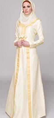 an off white kaftan with beige trim. love the silhouette and the rose details.