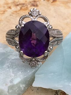 14k white gold ring set with a large deep purple amethyst that weighs approximately 4 carats. The lacy setting is set with small diamonds. Stones have been test