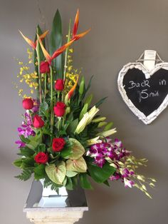 A large tropical arrangement with roses, orchids, anthurium, lillies and Heliconia