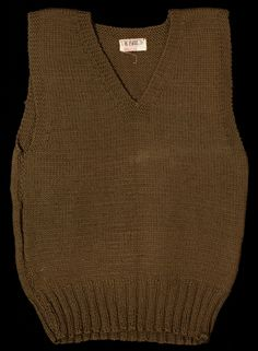 """SeaA knit wool pullover vest of the type distributed to the Armed Forces by the Red Cross. It is dark olive with a """"V"""" neck and a label at the back of the neck marked """"AMERICAN RED CROSS/ CHAPTER/ NOT TO BE SOLD/ WASHINGTON COUNTY/ HILLSBORO, OREGON"""" in red. 1940's"""