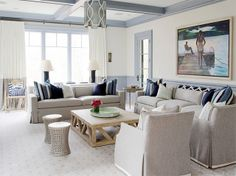 Living room with two neutral sofas with blue accent pillows, matching arm chairs, wood coffee table and two tone curtains