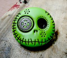 Happy round skull in green (avocado tone) with a steampunk wheel in his eye. Brooch, keychain, pendant or magnet (you choose)