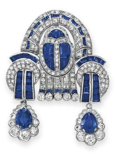 AN ART DECO DIAMOND AND SAPPHIRE BROOCH. Designed as a variously-cut diamond and sapphire sculpted plaque of geometric motif, suspending two pear-shaped sapphire and circular-cut diamond pendants, mounted in platinum, circa 1925, with pendant hook for suspension. #ArtDeco #brooch