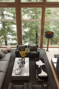 Interior Design Ideas - 17 Modern Living Rooms As Seen From Above | Not only have natural elements been included in the interior of this space, like the floor lamp, wooden coffee table, and flowers on the table, the large windows also make use of the scenery outside.