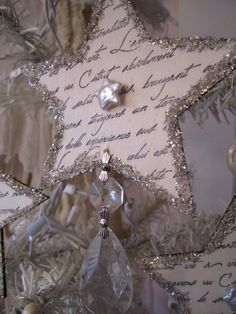 Search the web for French script handwritten notes (or find some in scrapbooking pages) for the star, back with thin cardboard (like from cereal boxes), trim in glitter (glitter glue, or use worn out tinsel garland that you were going to throw away), then dangle glass beads (chandelier style) from the bottom, and, Voila! (Add a mother of pearl button in the middle, and call it Christmas! :)