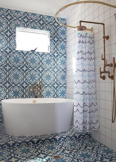 Exquisite Mediterranean themed bathroom is clad in Cement Tile Shop Bordeaux Tiles that cover the floor and an accent wall fitted with a window positioned above an oval freestanding bathtub with a floor mount tub filler. #tilebathtub