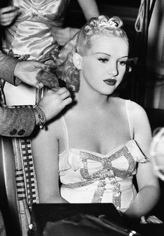 Betty Grable getting her hair brushed on the set of College Swing, 1938