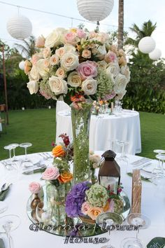 Tall arrangement table centerpiece with a mixture of ivory, pink and peach roses, orange snapdragon, queen anna lace and few green leafes