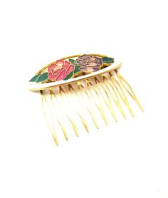 Vintage 1980s unmarked hair comb / hair accessory, gold in tone throughout, featuring an round oblong shaped focal featuring a white enamel boarder surrounding two roses, one red enamel and one purple enamel with green enamel foliage.    Condition: Great-some slight dirt of scuffing in gold tone metal in spots on back of hair comb.  Measurements: 2 1/2 x 2 Markings: None If you have any comments, questions, or concerns on this lot or any others, dont hesitate to send me a convo mess...