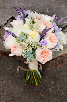 A garden style bouquet is made of garden roses, succulents and sprigs of lavender.