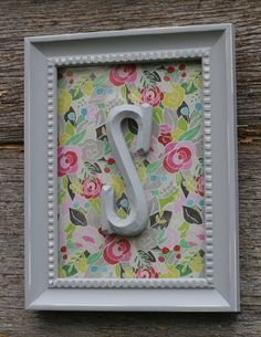 this would be easy to replicate.  glue the letter to the outside of the frame then you can change out the paper on the inside whenever you decide to change out color schemes