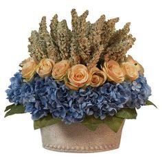 Create a lush tablescape or charming vignette with this blooming arrangement, featuring silk roses and blue hydrangeas in a glass vase.