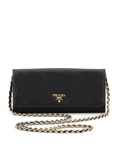"""Saffiano leather. Golden hardware. Chain-leather shoulder strap; 21 3/4"""" drop. Front flap with logo detail; snap-button corners. Inside, three bill slots, six card slots, zip compartment. 4""""H x 8 1/2"""""""