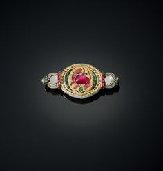 Brooch by Cartier, circa 1930, with mounts circa 1650-1750. Jade, inlaid with rubies, emeralds and diamonds. Al THani Colection