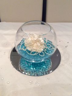 Fish bowl wedding centrepiece for blue themed weddings.  Blue beads and white flowers. Available to hire for your wedding in Swansea, Neath, port talbot, Bridgend, porthcawl, Llanelli, Carmarthen and surrounding areas of South Wales from affinity event decorators www.affinityeventdecorators.com