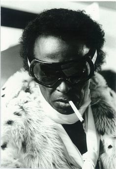 Miles Davis in fur, scarf, and superfly eyewear, ca. 1970s.