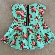 """""""Weekend Wear"""" HP Strapless Floral Peplum Top Pre-owned but still beyond beautiful. No stains or tears. Zipper down the front and semi-open back. Padding at top of shirt. A gorgeous mint color with floral print. Bound to get tons of compliments while wearing this pretty little piece! Topia Tops"""