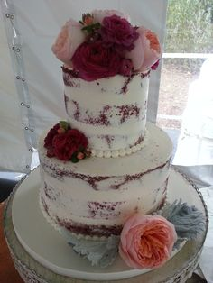 "Berry tone garden roses and renunculus were the perfect topping for this ""naked"" red velvet cake."
