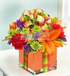 Send a present with true presence: our fresh bouquet of lilies, carnations, poms and more, beautifully hand-designed by our expert florists in a chic cube vase lined with a festive orange foam ribbon.