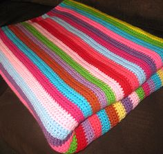 Level 6 - Make any size any color.  Great for doll blankets.  Handy to keep in the car.  Can make two of matching size, stitch them together and make a bag.  If you make one of the two pieces longer, it can fold over the other to serve as a flap.  Leave plain and geometric. OR Embellish with butterflies, pom-poms, or later, add curlicues, etc. - - Single crochet color stripes blanket.  GREAT VERSATILE PROJECT.