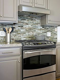 I like the color of these cabinets - especially with the backsplash and stainless steel appliances. 10 Kitchen Trends Here to Stay - recycled glass tile backsplash Centsational Girl Kitchen Redo, Kitchen Backsplash, New Kitchen, Kitchen Cabinets, Gray Cabinets, Green Kitchen, Kitchen Ideas, Backsplash Design, Grey Backsplash