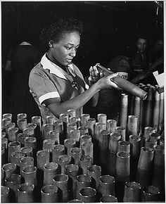 """Bertha Stallworth, age 21, shown inspecting end of 40mm artillery cartridge case at Frankford Arsenal."" ca. 1941 - ca. 1945 National Archives Identifier 535805"