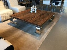 Couchtisch mit verchromten Tischbeinen. Couchtisch mit einer Tischplatte aus Altholz.