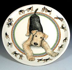 Young Airedale terriers are play specialists and this one would like to invite you to join in the fun. Tug, chase, ball, bitey face and stick rate highly on the dalepup play scale. This thrown and hand-painted porcelain platter is by Nan Hamilton