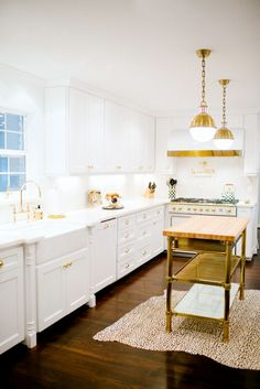 Glamorous white kitchen design with brass accents and hide rug