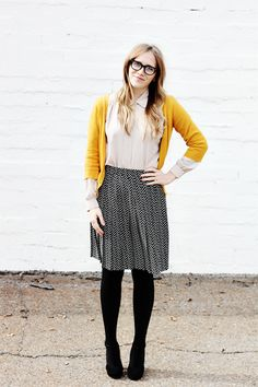 Mustard cardigan, black tights, heels, and polka dot skirt