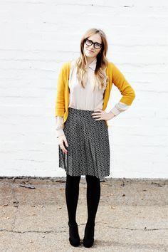 Mustard cardigan, black tights, heels, and polka dot skirt