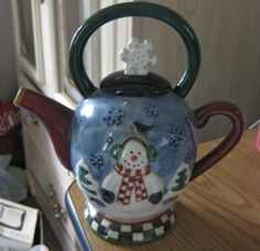 "This item is a snowman teapot by Debbie Mumm and made by Sakura.  He is dressed in red checked scarf and is wearing earmuffs and a bird is sitting on his head.  There is a snowflake on the lid.  There is also another handle on the top. This teapot measures 7"" tall including the top handle, 7"" wid..."