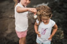 girls on a beach looking for shells