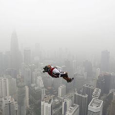 A base jumper leaps from the 300-metre high Kuala Lumpur Tower during the International Tower Jump on Oct. 2. He is one of more than 100 people who base jump on a hazy day in Kuala Lumpur Malaysia. Photograph by Olivia Harris@reuters. by time
