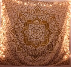 A beautiful mandala tapestry design with warm toned fairy lights.