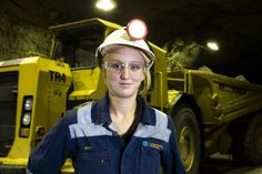 Female miner (no name) underground with head lamp in front of big yellow mining truck (good generic)