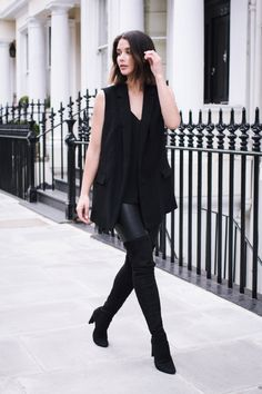 Sara Donaldson wears the all black trend with an oversized waistcoat and over the knee boots. Waistcoat/Vest: Zara, Leather trousers: J. Brand, Boots: Stuart Weitzman.