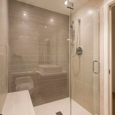 This modern bathroom has a large glass-enclosed shower in tile. The shower stall includes a bench and recessed lighting Shower Remodel, Bath Remodel, Beautiful Small Bathrooms, Master Bathrooms, Contemporary Bathrooms, Bathroom Lighting Design, Recessed Lighting In Bathroom, Relaxing Bathroom, Spa Like Bathroom