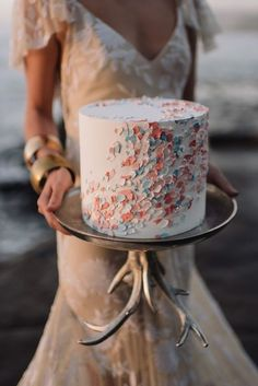 Confetti-inspired wedding cake with an antlered stand