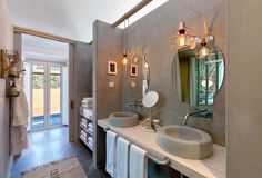 Tranquil bathroom with stone sinks and hanging lighting. By: SegmentoPonto4