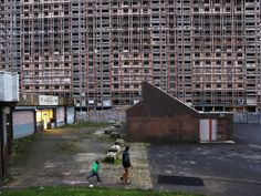 A chemist's shop shines out next to the Red Road flats as they await demolition in Glasgow.