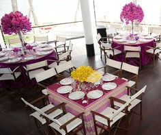 Tables set in pink and purple linens are topped with brightly colored arrangements of pink Phalaenopsis orchids and yellow Mokara orchids.