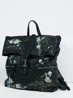 Violet Storm Leather Backpack   Beautiful leather backpack featuring floral details with a pretty painted-on look and stud accents allover. Pull handle with adjustable straps for an easy carry. Foldover top with clip and snap button closures. Outer zip pockets. Lined inner.