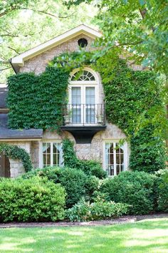 Home exterior with climbing vines and Juliet balcony.