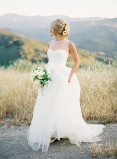 I like the sheer top on this wedding dress.. and the rolling hills behind her, of course.