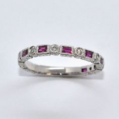 Emerald cut rubies and round diamonds, set in 18k white gold.